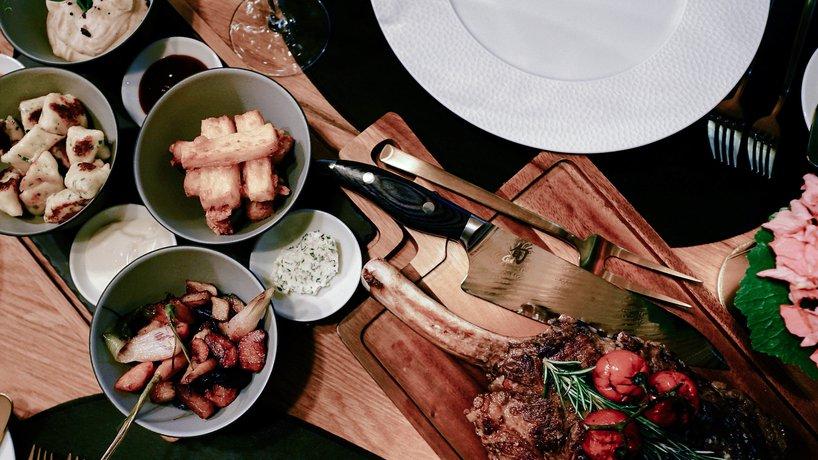 21 Tage Dry aged Rindstomahawk-Steak mit Gartenkräuter-Frischkäse Gnocchi, Geräucherte Polenta Fries, Wurzelgemüse-Püree, Geschmorte Rüben und vier Saucen.