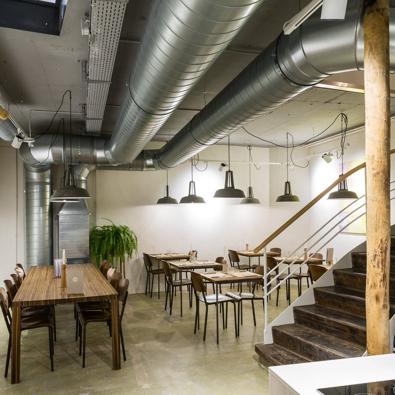 Minimalistisch-rustikales Ambiente. Gaststube im Untergeschoss, wo sich auch die offene Küche befindet.