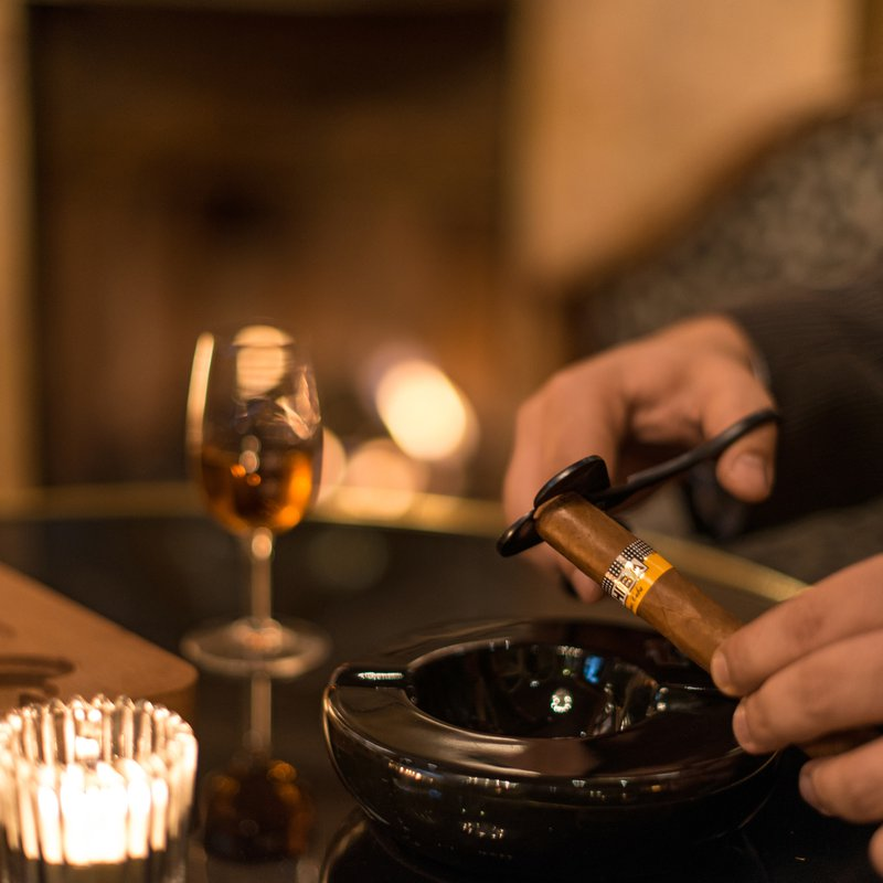 Rum, Zigarre und Kaminfeuer im Hintergrund