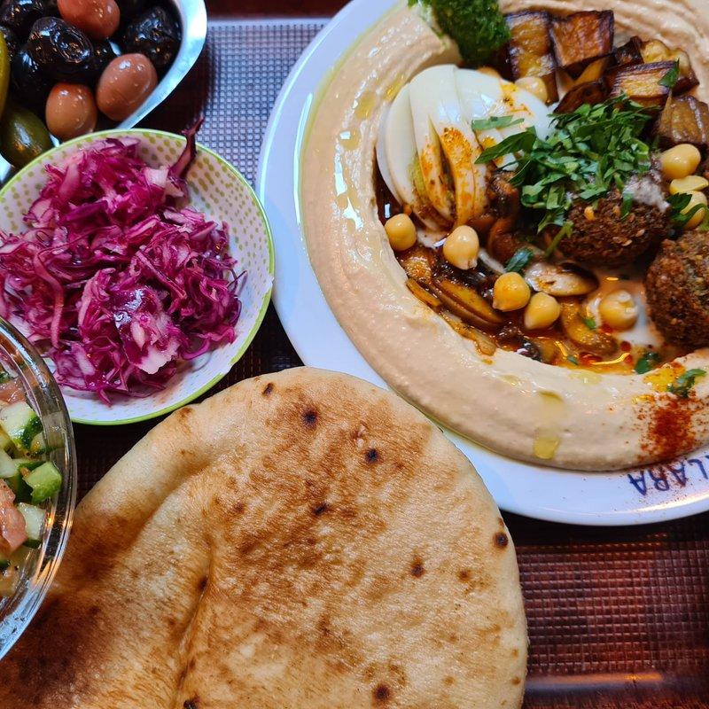 Hummus Sababa: Hummus Teller mit warmen Pilzen, Bio-Ei, Falafel, Tahina, Olivenöl, Salat und Oliven